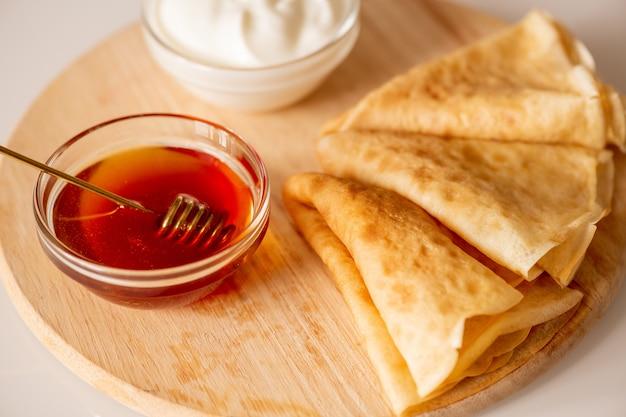 Due piccole ciotole di vetro con panna acida e miele fresco in piedi sul tagliere con tre frittelle fatte in casa piegate