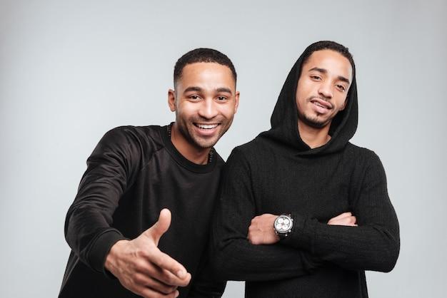 Due giovani africani sorridenti che stanno e che indicano su voi
