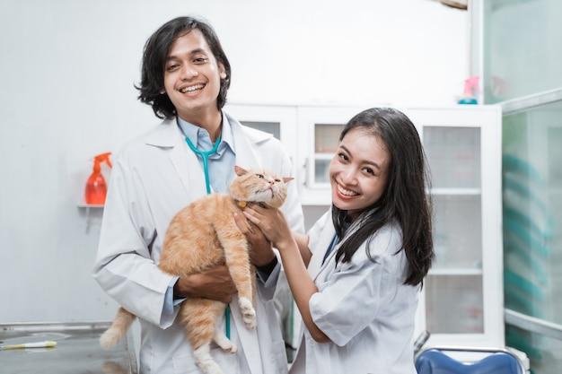 Due veterinari asiatici sorridenti che guardano mentre controllano il gatto marrone presso la clinica veterinaria