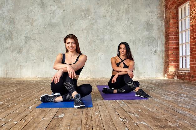 Due belle ragazze sorridenti di forma fisica che fanno le esercitazioni nella stanza di forma fisica sulle stuoie. concept sport, lavoro di squadra.
