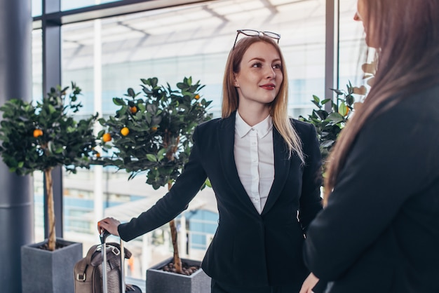 Due soci commerciali sorridenti che parlano che stanno nell'aeroporto