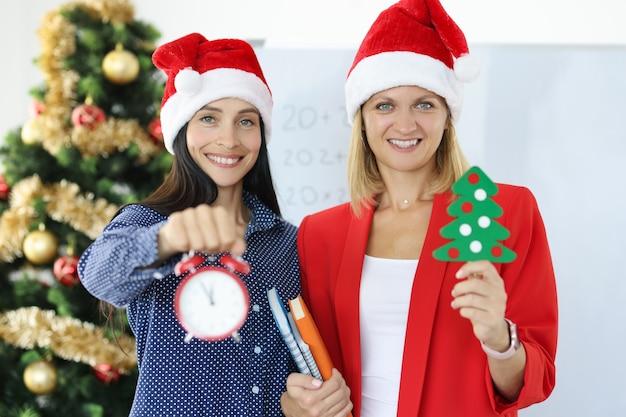 Due donne d'affari sorridenti in cappelli di babbo natale che tengono una sveglia sullo sfondo dell'albero di natale. pianificazione dello sviluppo aziendale per il concetto dell'anno in anticipo