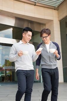 Due uomini d'affari sorridenti che camminano e parlano in città
