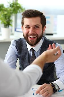 Due uomini d'affari sorridenti dell'impiegato deliberano sul problema all'ufficio