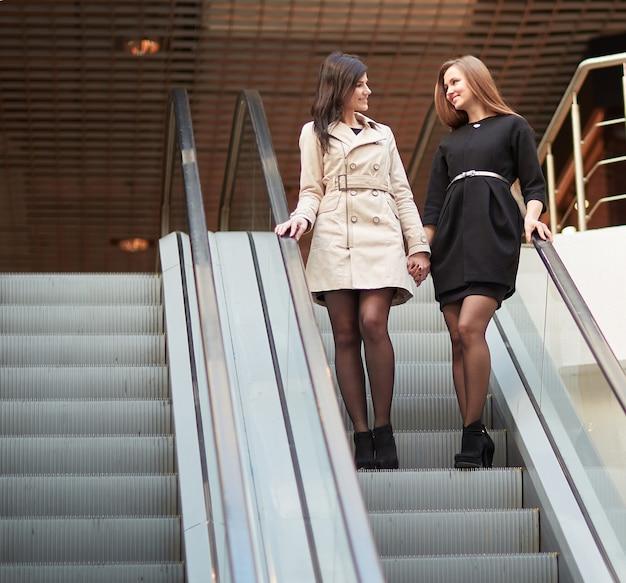 Due dipendenti sorridenti in piedi su una scala mobile nel business center. concetto di affari