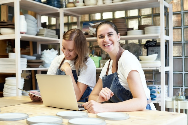 Imprenditore femminile sorridente due con il portatile in laboratorio artigianale.