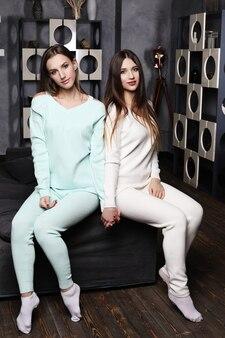 Due donne sorridenti degli amici che si siedono sul divano che guarda l'obbiettivo nel salotto di casa