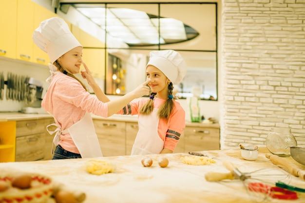 Due bambine sorridenti cuochi in berretti e grembiuli divertendosi, preparazione di biscotti in cucina. bambini che cucinano pasticceria, bambini chef che preparano la torta