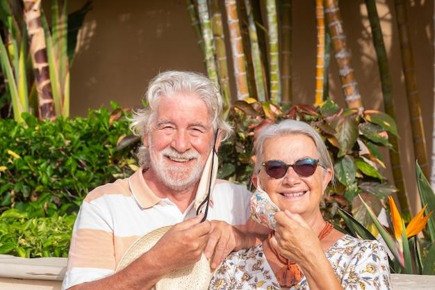 Due anziani sorridenti che si tolgono la maschera medica dopo la quarantena a casa godendosi la libertà