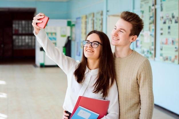 Due studenti sorridenti che prendono selfie nell'edificio universitario, divertendosi insieme