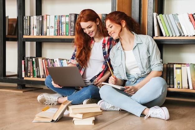 Due ragazze adolescenti sorridenti che si siedono su un pavimento allo scaffale per libri