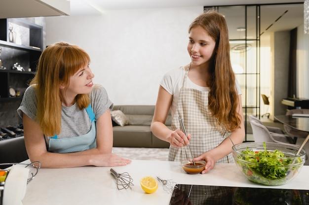 Due donne sorridenti tagliano insalata verde con pomodori e mescolano il condimento in una piccola ciotola con succo di limone, salsa scura e olio in cucina at