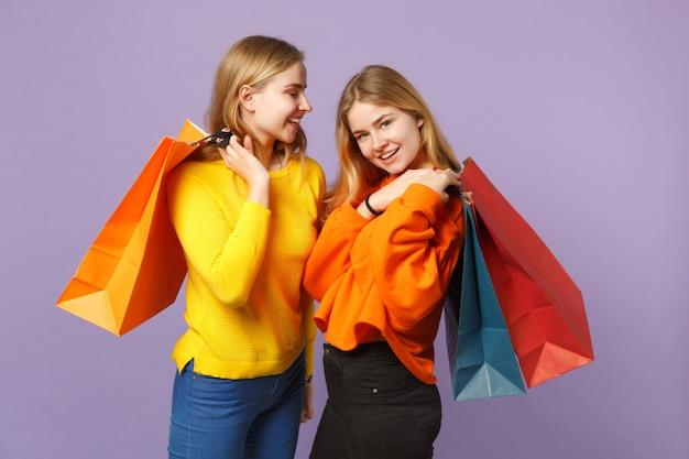 Due giovani sorelle gemelle bionde sorridenti in abiti vivaci che tengono la borsa del pacchetto con gli acquisti dopo lo shopping isolato sulla parete blu viola. concetto di stile di vita familiare di persone.
