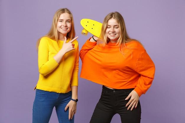 Due giovani sorelle gemelle bionde sorridenti in abiti vivaci che puntano il dito indice, tenendo in mano uno skateboard giallo isolato sulla parete blu viola. concetto di stile di vita familiare di persone.
