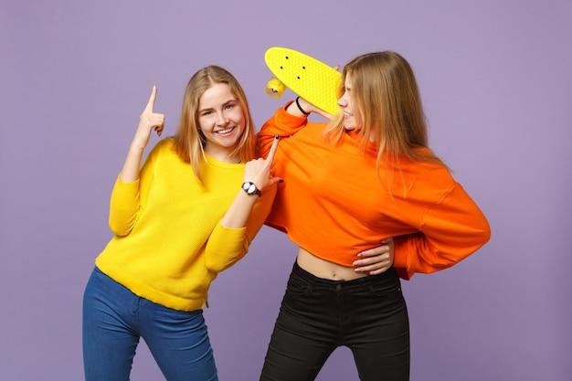 Due giovani sorelle gemelle bionde sorridenti in abiti vivaci che puntano il dito indice verso l'alto, tengono lo skateboard giallo isolato sulla parete blu viola. concetto di stile di vita familiare di persone.