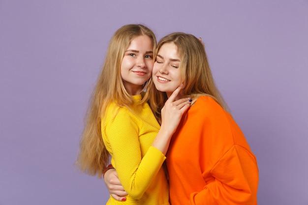 Due giovani sorelle gemelle bionde sorridenti in abiti colorati vividi che abbracciano e isolate sulla parete blu viola pastello. concetto di stile di vita familiare di persone.