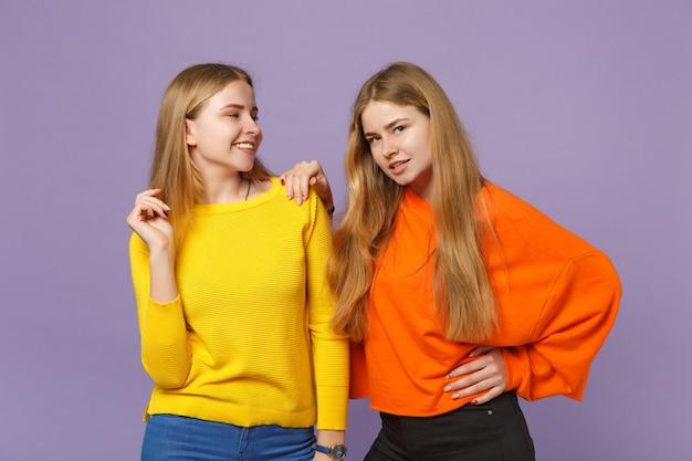 Due giovani sorelle gemelle bionde sorridenti in abiti colorati vividi in piedi, da parte isolate sulla parete blu viola pastello. concetto di stile di vita familiare di persone.
