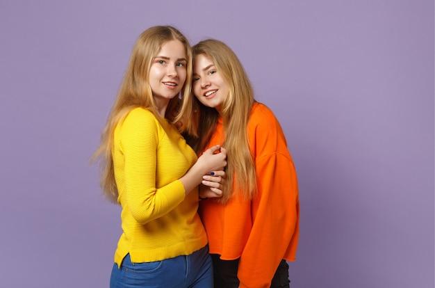 Due giovani sorelle gemelle bionde sorridenti in abiti colorati vividi in piedi, isolate sulla parete blu viola pastello. concetto di stile di vita familiare di persone.