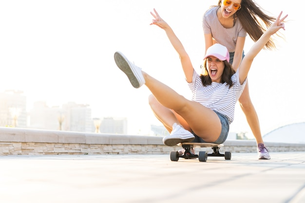 Due ragazze sorridenti che si divertono mentre cavalcano su uno skateboard al parco.