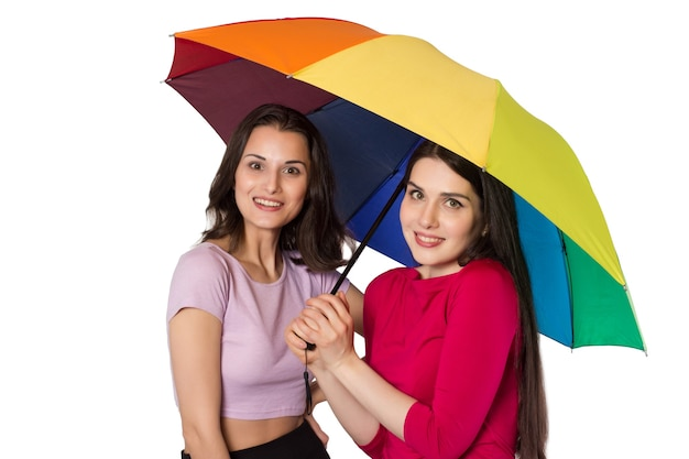 Due giovani donne sorridenti con ombrello arcobaleno.