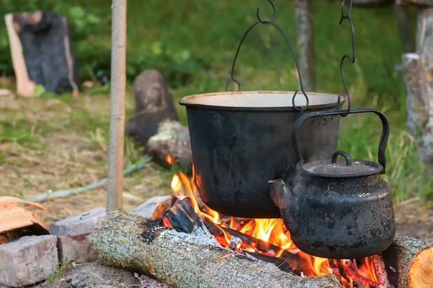 Due bollitori turistici affumicati sul fuoco da campo. processo di cottura sulla natura