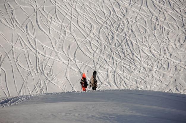 Due snowboarder con l'attrezzatura camminando sul sentiero sullo sfondo di tracce sul pendio nella famosa località turistica di gudauri in georgia