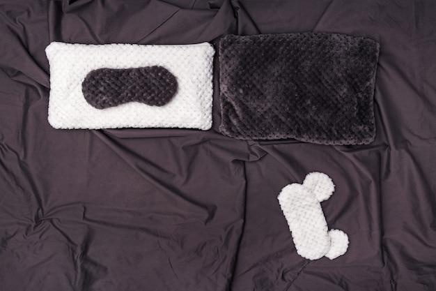 Due cuscini morbidi e due maschere per dormire su un foglio sgualcito grigio scuro