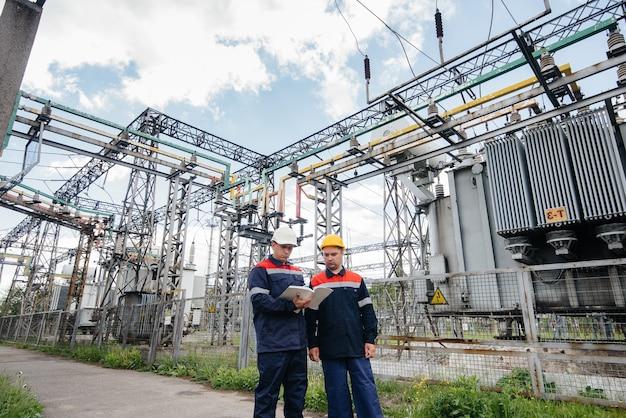 Due ingegneri specializzati nella sottostazione elettrica ispezionano le moderne apparecchiature ad alta tensione. energia. industria.