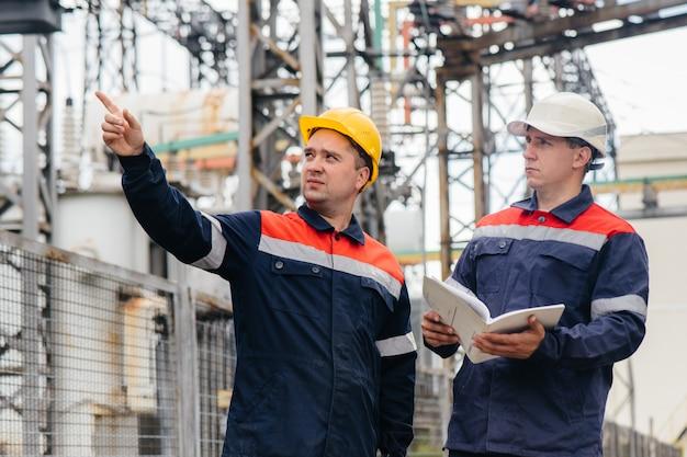 Due ingegneri specializzati nella sottostazione elettrica ispezionano le moderne apparecchiature ad alta tensione