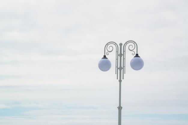 Lampada di via sferica due sulla colonna d'annata bianca sul fondo del cielo leggero con lo spazio della copia. lampione.