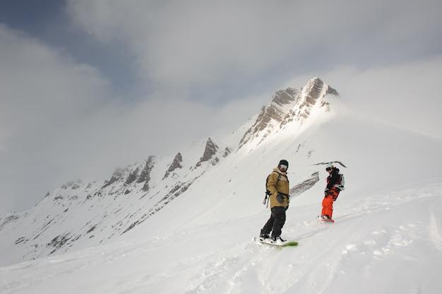 Due sportivi in abiti sportivi pesanti che scivolano sullo snowboard dalla cima della montagna