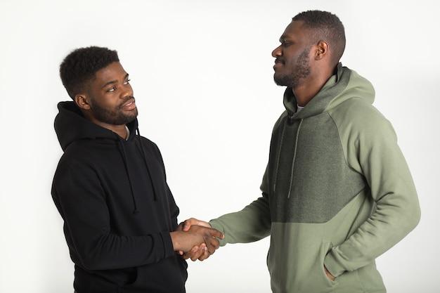 Due uomini africani sportivi in tute da ginnastica su sfondo bianco si stringono la mano