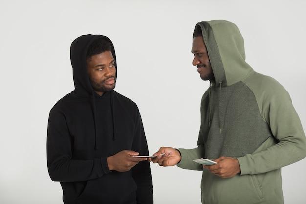 Due uomini africani sportivi in tute da ginnastica su uno sfondo bianco con i dollari nelle loro mani
