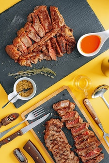 Due bistecche di controfiletto e t-bon, mediamente cotta, su fondo di pietra. concetto di cena per due