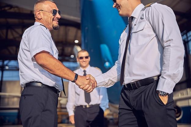 Due hostess e tre piloti trascorrono del tempo insieme nell'hangar dell'aviazione mentre si gode il bel tempo all'aria aperta
