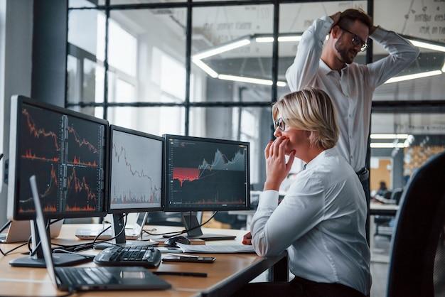 Due agenti di cambio in abiti formali lavorano in ufficio con il mercato finanziario.