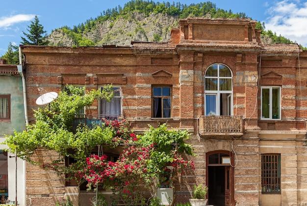 Casa in mattoni a due piani con uva e rose in fiore. casa di mattoni a due piani.viaggio in georgia