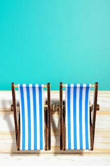 Due sedie a sdraio a strisce su una superficie di legno e sfondo blu