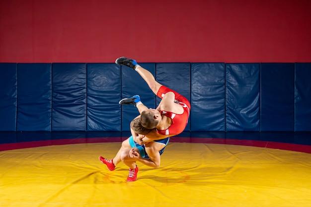 Due lottatori forti in calzamaglia da wrestling blu e rosso stanno lottando e facendo un salto all'anca su un tappeto da wrestling giallo in palestra. il giovane che fa afferra.