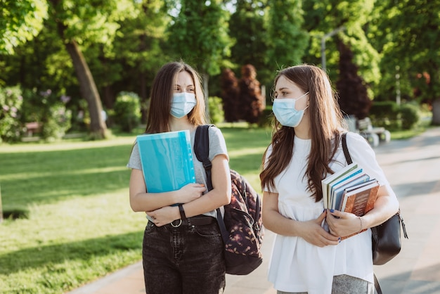 Due studentesse con maschere mediche protettive camminano e parlano nel campus. educazione a distanza. messa a fuoco selettiva morbida.