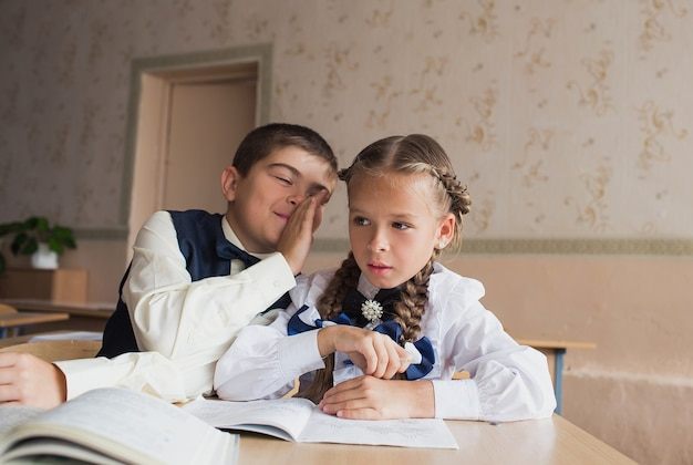 Due studenti, un ragazzo e una ragazza, siedono a una scrivania a scuola e comunicano tra loro nell'orecchio.