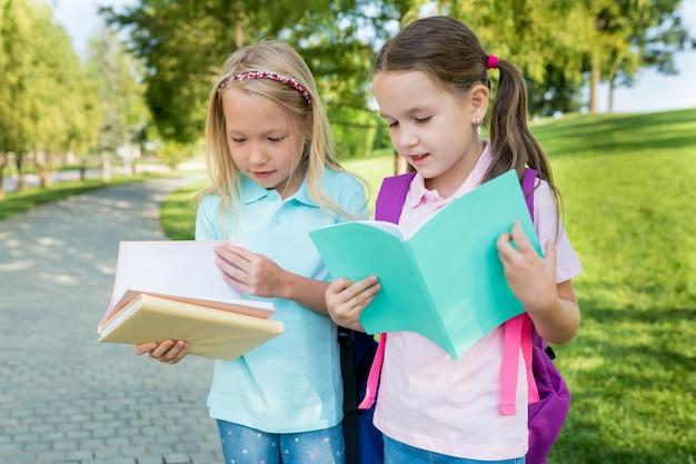 Ragazza di due studenti con zaini e libri che camminano vicino alla scuola il primo giorno