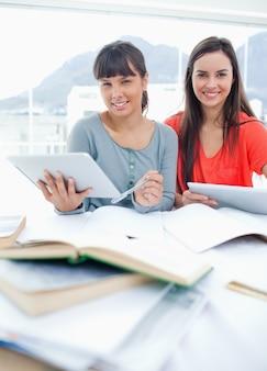 Due studenti con i tablet in mano mentre si siedono e fanno i compiti