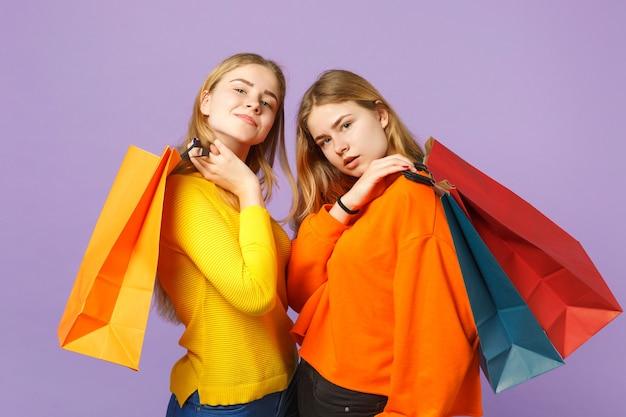 Due splendide giovani sorelle gemelle bionde in abiti vivaci tengono il pacchetto con gli acquisti dopo lo shopping isolato sulla parete blu viola. concetto di stile di vita familiare di persone.