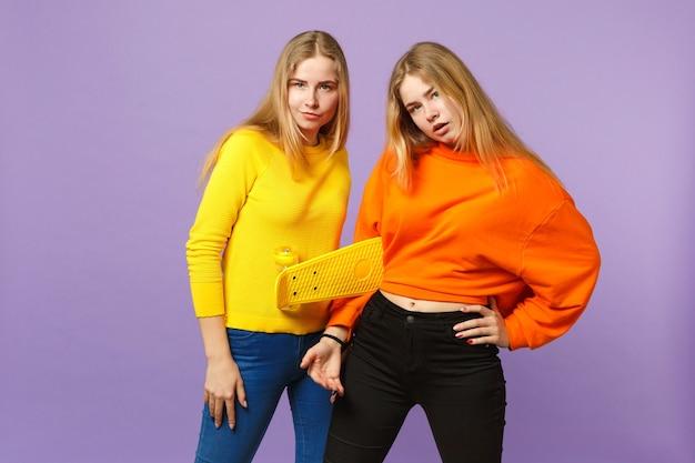 Due splendide giovani sorelle gemelle bionde ragazze in abiti colorati vividi che tengono skateboard giallo isolato sulla parete blu viola pastello. concetto di stile di vita familiare di persone.