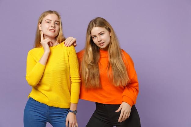 Due splendide giovani sorelle gemelle bionde in abiti colorati vividi in piedi, isolate sulla parete blu viola pastello. concetto di stile di vita familiare di persone.