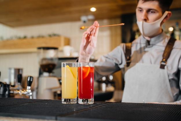 Due baristi alla moda in maschere e divise durante la pandemia, preparano cocktail. il lavoro di ristoranti e caffè durante la pandemia.