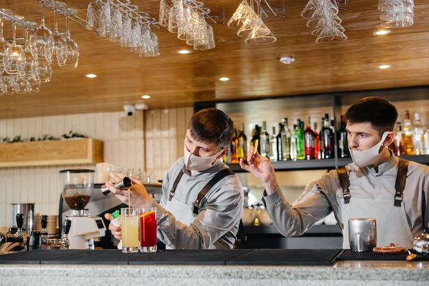 Due baristi alla moda in maschere e divise durante la pandemia, preparano cocktail