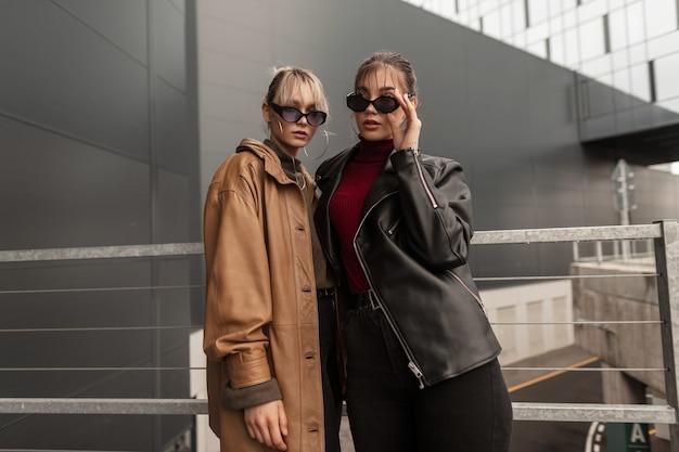 Due belle giovani sorelle eleganti in abiti di pelle alla moda con jeans neri e occhiali da sole vintage stanno in città