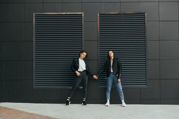 Due ragazze alla moda si tengono per mano contro un muro nero